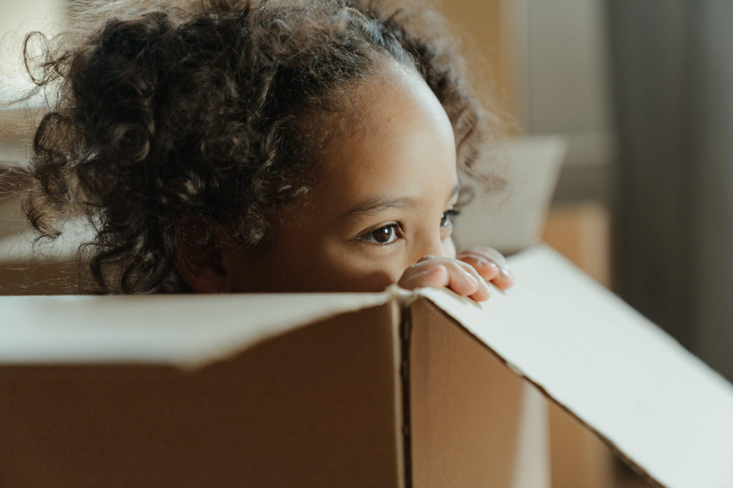 Little girl in a cardboard box